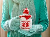 Little toy snowman in a winter cup in female hands. Woman hands in teal mittens holding a knitted cup with a cute tiny snowman-toy sneaking out of it. Winter time and Christmas present concept.