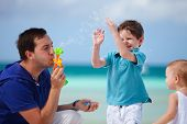 pic of family vacations  - Father and two kids on tropical beach playing with soap bubbles - JPG