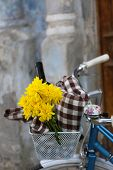 Old bicycle with flowers and checkered blanket in metal basket on old wall background