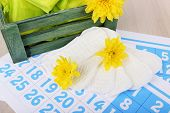 Sanitary pads in dark green box and sanitary pads and yellow flowers on blue calendar background