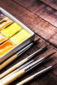 Water Color Drawing, Colorful Aquarelle Paints And Brushes Over Vintage Wooden Background Close Up.