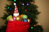 Red bag with Christmas toys on Christmas tree background