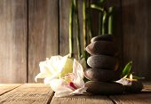Spa stones, white orchid and bamboo branches on wooden table on wooden wall background