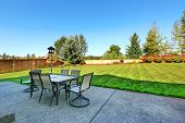 image of lawn chair  - Patio area overlooking backyard landscape. Dining table with chairs and lantern ** Note: Shallow depth of field - JPG