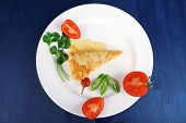 food : cheese casserole piece over white plate served with peppers and tomatoes on blue table