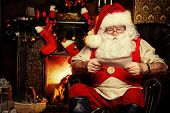 stock photo of christmas claus  - Santa Claus standing at home with gifts - JPG