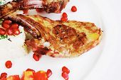 meat food: ribs on white plate with rice garnish and tomatoes over white background