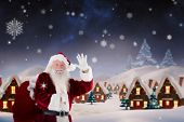 Santa claus waving against snowy landscape with fir trees