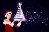Pretty girl presenting in santa outfit against glowing christmas tree
