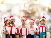 family, happiness, generation, holidays and people concept - happy family in santa helper hats with gift boxes sitting on couch over lights background