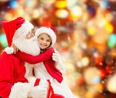 holidays, christmas, childhood and people concept - smiling little girl hugging with santa claus over red lights background