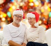 family, holidays, christmas, age and people concept - happy senior couple in santa helper hats sitting on sofa over red lights background