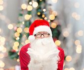 christmas, holidays and people concept - man in costume of santa claus blowing on palms over tree lights background