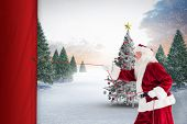 Santa pulls something with a rope against christmas tree in snowy landscape