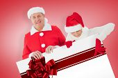 Festive couple showing poster against red christmas ribbon
