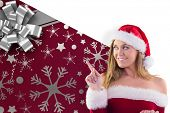 Festive blonde smiling and pointing against christmas wrapping paper with bow