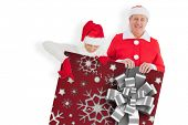 Festive couple showing poster against christmas wrapping paper with bow