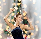 people, party, holidays and glamour concept - smiling woman dancing with raised hands over christmas tree lights background