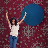 A young happy woman stands with her hands in the air against red vignette