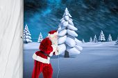 Santa claus pulling rope against white snowy landscape with fir trees