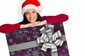 Woman smiling at the camera against christmas wrapping paper with bow