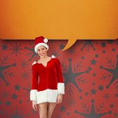 Pretty santa girl smiling at camera against orange