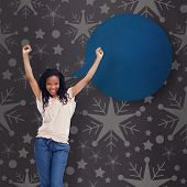 A young happy woman stands with her hands in the air against grey vignette