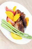 meat food : grilled red beef fillet with mango tomatoes and asparagus , served on white dish over wo