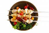 fresh raw chicken kebabs served on dark plate