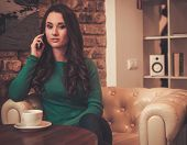 Young woman with cup of coffee talking over mobile phone