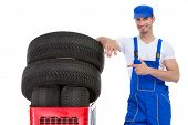 Cheerful mechanic pointing in new tires in shopping cart