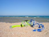 Snorkel gear on a yellow sandy beach lying near upon coast