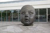 MADRID, SPAIN - OCTOBER 9, 2014: Baby Head Statue at the Atocha Train Station in Madrid. Created by Artist Antonio Lopez, the statue stands three meters high, made of bronze and weighs 2,000 kilos.