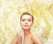 beauty, people and jewelery concept - beautiful woman with pearl earrings and necklace over yellow lights background