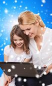 family, childhood, holidays, technology and people concept - smiling mother and little girl with laptop computer over blue snowy background