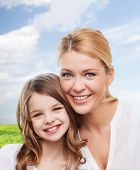 family, childhood, happiness and people - smiling mother and little girl over blue sky and grass background