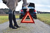 Broken car, girl and warning triangle