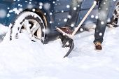 transportation, winter, people and vehicle concept - closeup of man digging snow with shovel near car
