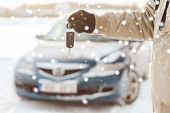 transportation, people, season and ownership concept - close up of man with car key outdoors