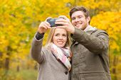 love, relationship, family and people concept - smiling couple hugging and taking selfie in autumn park