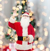 christmas, holidays, gesture and people concept - man in costume of santa claus waving hand over tree lights background