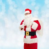 christmas, holidays, gesture and people concept - man in costume of santa claus with bag showing thumbs up over blue lights background