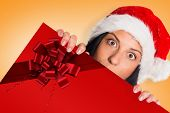 Woman surprised at the camera against red christmas ribbon