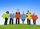 Business People Holding Jigsaw Puzzle Pieces Outdoors