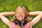 Laughing girl with headphones lays on green grass