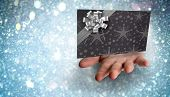 Hand bursting through paper against white snow and stars design