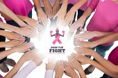 Hands joined in circle wearing pink for breast cancer against breast cancer awareness message