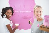 Smiling housemates painting wall pink against pink breast cancer awareness ribbon