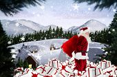 Santa walking on pile of gifts against cute village in the snow
