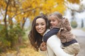 Young mother with her little daughter walking in fall park on yellow fallen leaves one autumn day